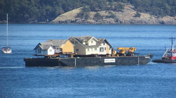 Image: Houses from Oak Bay, B.C., are shipped by barge to San Juan Island, Washington. Photo: Nancy DeVaux